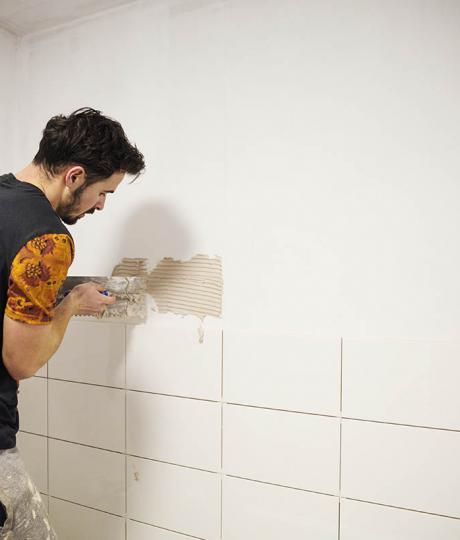 man in surrey tiling a bathroom wall