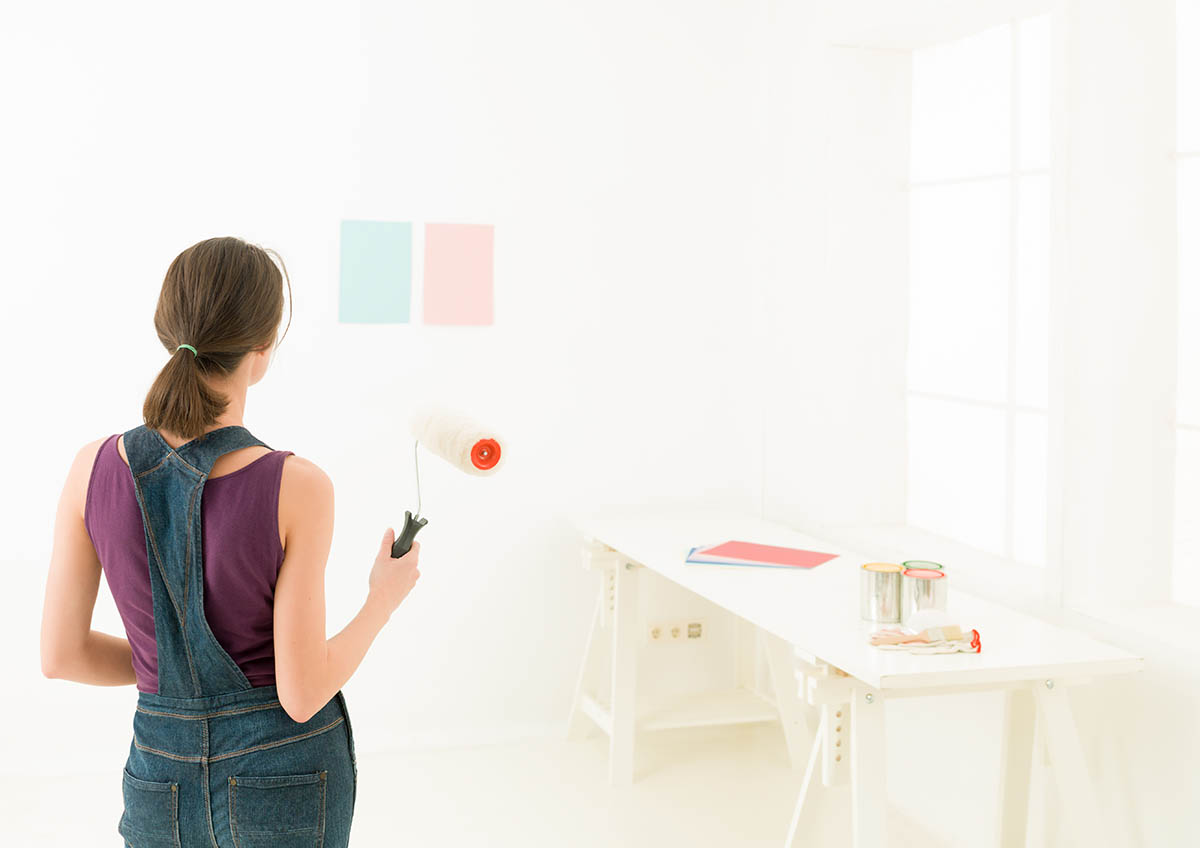 woman comparing colours on wall before painting interior walls